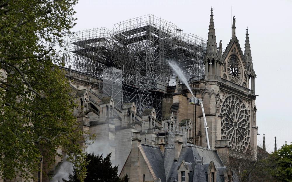 Bombeiros ainda jogam água em alguns pontos da Catedral de Notre-Dame — Foto: Zakaria Abdelkafi / AFP Photo