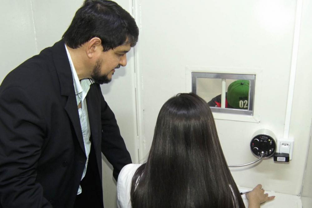 Sob orientação do professor Irajá, estudante presta atendimento a detento no parlatório / Foto: Divulgação