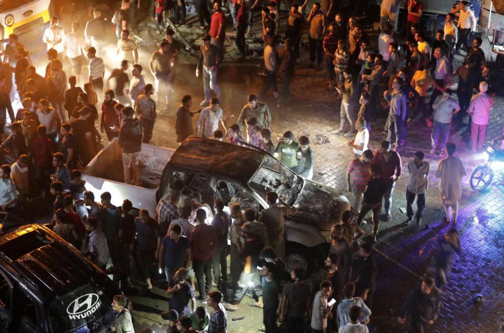 Multidão se aglomera em local onde carro-bomba explodiu neste domingo (2), em Azaz, na Síria — Foto: Khalil Ashawi/Reuters