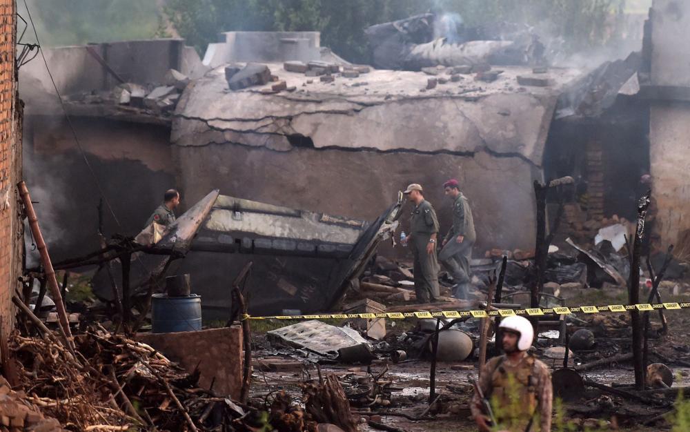 Soldados paquistaneses isolam local onde avião militar caiu em Rawalpindi, na terça-feira (30) — Foto: Aamir Qureshi/AFP